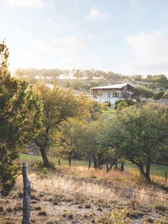 "While the home is located in a ranch-style neighborhood surrounded by other houses, the plots are large enough to make it feel like a remote area. ""Before we started designing, we brought tents and camped on-site,"" says architect Ryan Bollom. ""You can watch the sun rise over the east hills, set over the west hills, and enjoy the stars at night. The place just brings a sense of calm and relaxation."""