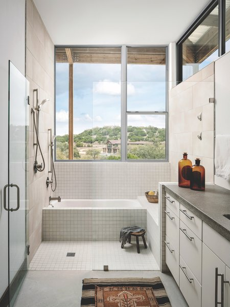 Every room in the house has access to natural light. The bathroom cabinets are standard mid-grade factory-built cabinets, topped by custom poured concrete countertops that the architects designed and built.