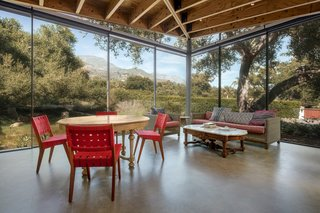 "Every room in the house has a view out to the landscape and another up into the trees or the sky. ""In some places, you will see a branch or a treetop framed by a skylight, and in other places it's about looking up at the changing sky,"" says architect Peter Tolkin. The casual dining and lounge area in the kitchen volume, for example, looks over the hills in the distance."