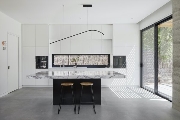 The backsplash in the kitchen is a frameless sliding window that offers natural cross ventilation. It currently frames the ti-tree fencing, but as the landscaping grows greenery will be visible.