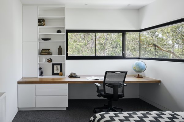 """I love to use different window shapes to frame views in different and unexpected ways to create interest and provide a unique experience to a particular space,"" says architect Kirsten Johnstone. ""For example, the corner window in the upstairs bedroom, with a deep boxed reveal above the study bench, is completely different from the principal bedroom with a huge picture window—yet both frame quiet views of the treetops. I believe it gives a room identity and forms what I hope are joyful memories."""
