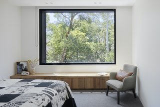 The principal bedroom has a generous picture window facing east, and a timber bench with drawers below. A north-facing window provides natural ventilation across the bed and protected views over the trees.