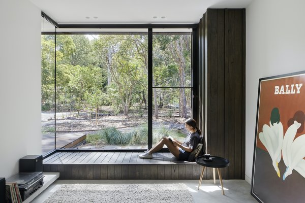"""""""There is something inherently playful about sitting on a deep window ledge with a book,"""" says architect Kirsten Johnstone. """"Throughout the home, the juxtaposition of public versus private spaces and exposure versus protection is explored in different ways. In the lounge retreat, the large corner window abuts the hidden front entry door, and the stepped-down room means this bench seat is at the same level as the front entry decking. The external wall cladding wraps into the room, blurring the line between the inside and the outside and creating a delightful nook that is almost in the garden. It also provides an opportunity for engagement with neighbors and passers-by—a connection, a wave, a glimpse."""""""
