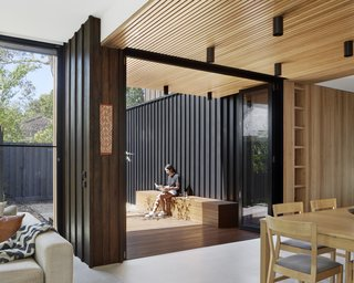 A built-in box seat on the timber deck adjoining the dining area offers an outdoor space for an enjoyable moment in the sun. This area is shaded by deep eaves formed by the extension of the timber batten ceiling outside.