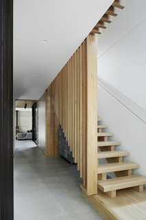 A timber platform forms the first step of the open timber staircase in the entry hallway, which leads into the dining and living space.