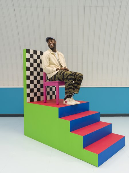 Yinka sitting on one of the boldly colored, elevated chairs he created for his A Large Chair Does Not Make a King installation at the 2017 London Design Festival.
