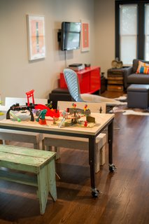 Looking back from the children's play area to the living room, which features a bright red credenza from IKEA and other orange accent pieces.