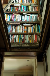 The glass ceiling doubles as the stair landing between the first and second floors, and provides a view up to the library built into the landing.