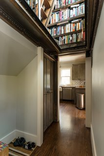 The glass landing beneath the library in the stairwell allows for constant natural light into the once-dark mudroom. The entry hall leads directly to the kitchen.