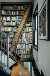 Metalworker Rick Gage made the library's custom bookcase on the remnants of the home's original, Depression-era second staircase which dates back to when the home was a duplex. A pullout ladder provides access to the books.