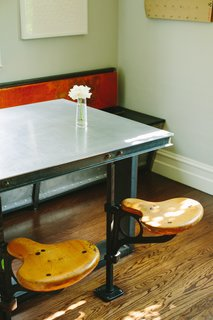 In the diner-style eating area, a custom aluminium table top is surrounded by salvaged-wood bench and vintage swivel seats.