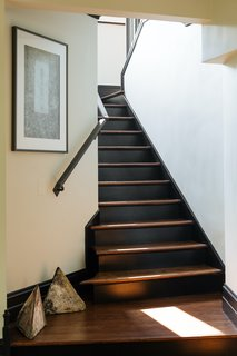New wood stairs were installed and stained dark brown to contrast against crisp white walls. A custom iron handrail was made to follow the curve of the stairway.