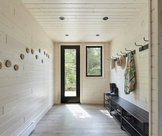 """The entry hall has space to store boots and coats as you come into the home. The flooring throughout is high-quality vinyl that mimics the effect of a timber floor. """"At first, I thought, 'Everything else in this house is wood, how can we do a vinyl floor?,'"""" says architect Tom Knezic. """"But nobody would do a hardwood floor in a cottage, because you don't heat it all winter and they tend to buckle. The vinyl is a very premium product, and it looks fantastic—but it can freeze and get wet. It was perfect because you don't have to worry about the kids coming in with wet clothes, or with sand on their feet."""""""