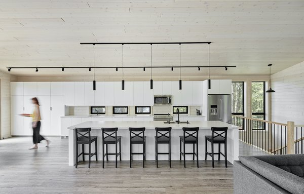 The kitchen opens out into the dining room and living area, and features an island countertop from Caesarstone. The lighting throughout is from Lightline.