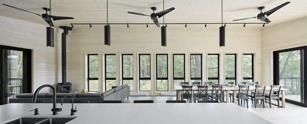 """Normally, we do large windows,"" says architect Tom Knezic. ""But for this project, all the windows had to be carried onto a barge to come across the channel and then carried up through the forest into the building. So, all the windows were made small—especially those south windows, because that's about the maximum two people can carry."" There are large glass doors—which came disassembled—at both ends of the open-plan living space, which allows for a cross breeze through the space."