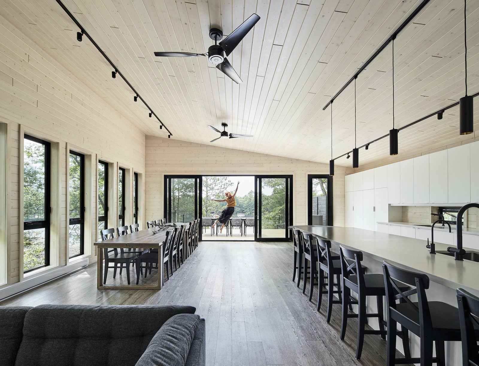 Dining room and kitchen of Kahshe Lake Cottage by Solares Architecture.