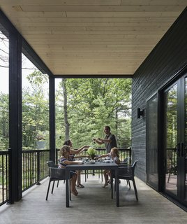 "The screened porch at the rear of the property overlooks the forest, and it was a response to the request of architect Tom Knezic's mother for a space that embraced the morning light from the east. ""I got a lot of head scratching from people wondering why you would put a porch on the back—but it's actually kind of nice to look at the forest, and you get the east light,"" says Knezic. ""It also means we have three aspects, while it's more typical to have just the single aspect toward the lake."""