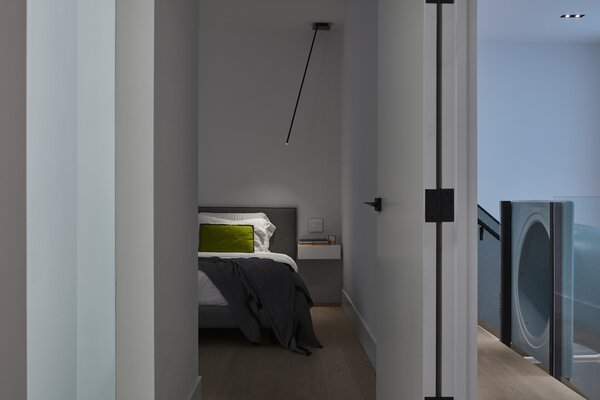 The master bedroom has been designed so that the doors can be left open for the children at night without compromising privacy. To facilitate this, a series of nightlights integrated into the hall lead the way from the childrens' bedrooms in the basement level to the master bedroom. In the bedroom Peled Soffitto lights from Viabizzuno make it easy for one of the couple to read while the other sleeps.