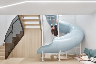Inside, the home has been designed as a fun space to bring the family together—including the installation of a blue slide that connects the two levels of the home.