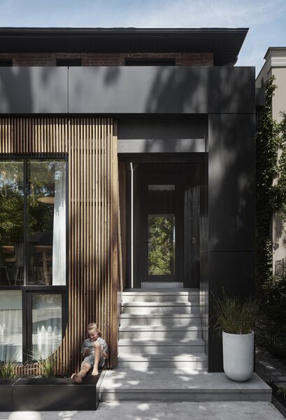 """""""One of the clients' families has a history of being heavily involved in beautiful vintage wooden boats,"""" says architect Trevor Wallace. """"The timber screen plays off that idea and introduces a very warm, natural material to face the street."""" The timber screen wraps around the side window to offer added privacy from the main entrance."""