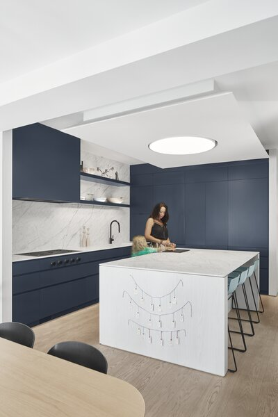 "The large kitchen is a space for the family to gather, with a stone-look porcelain benchtop and splashback from Stone Tile. ""The clients wanted the stone in the kitchen to feel natural rather than dramatic,"" says architect Trevor Wallace. ""It's large format porcelain, though, as I don't think they would have been able to handle the level of patina that would have developed on a natural stone when cooking with children!"""