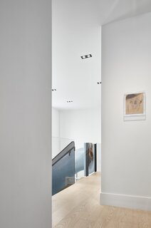 """The long hallway runs past a double-height volume and overlooks the basement level. """"Two big windows allow natural light to reach the basement from the ground floor,"""" says Wallace. """"Because of this, the experience of being in the basement feels as little like being in a basement as possible."""""""
