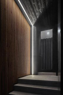"""The main entrance is clad in dark timber treated using the Japanese technique of Shou-Sugi-Ban. """"We created this darker entry point and then introduced very contemporary lighting to illuminate that space and to denote that the renovation was speaking a very different language,"""" says architect Trevor Wallace. """"With any sort of entry into domestic design it's nice to have a moment of transition."""""""