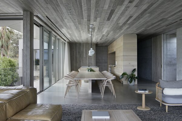 The kitchen and dining area opens out to a narrow balcony that overlooks the internal courtyard and has views over the bay. The DC09 dining chairs are by Inoda + Sveje for Miyazaki Chair Company, and sourced from Great Dane Furniture.