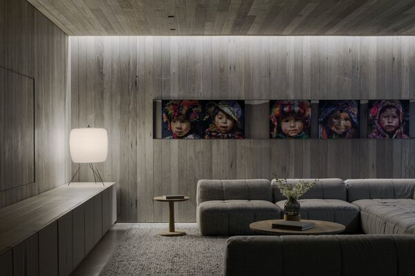 The basement living room is smaller and more private, offering a dark space for watching movies as a family. Like the first-floor living room, the television is concealed by a timber screen. The artwork is by Columbian-born, Melbourne-based painter Julian Clavijo.