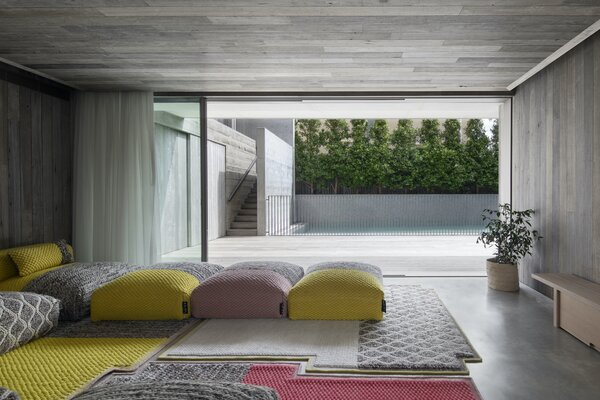 """The sitting room on the ground floor features a Mangas Space Plait modular sofa by Patricia Urquiola for Spanish brand Gan, from Hub Furniture in Melbourne. """"The materials had to essentially take a back seat to the view and the internal soft furnishings, which is where all the vibrancy and color would come from, along with the occupants and what they would bring to the table,"""" says architect Tony Vella. """"A clear undertaking from our client was to avoid painted, rendered, tiled, or applied finishes at all costs—which was not an easy task!"""""""