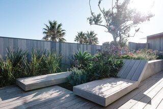 Sun loungers are integrated into the roof terrace, which features timber decking and lush landscaping.