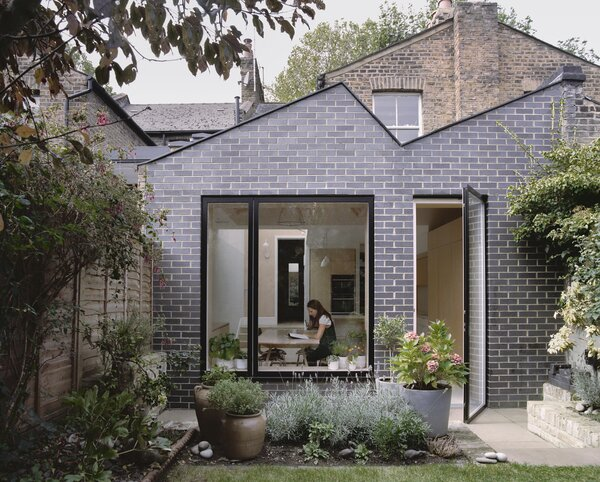 """The rear extension is clad in Brunel smooth blue brick. """"I chose a dark, gloomy color to complement the dark blue iron spot in the London stock brick that the rest of the house is made of,"""" says Julia. """"I wanted it to be different and feel like a contemporary addition that speaks of its time."""""""