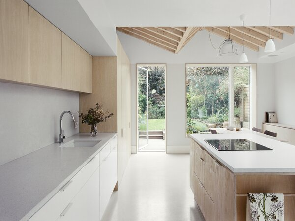 The rear extension features a large picture window that allows for a strong connection with the garden without the visual distraction of a folding door frame. The powdery pink concrete resin floor is from Pure Floor.