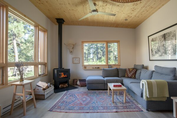 The simple living room features a wood-burning stove to keep the space cozy in colder months. The interior material palette was kept simple and practical. The ceilings and trims are pine, while doors are crafted from hemlock timber.