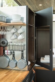 Pots, pans, cutlery, and shelves are hung on a pegboard wall in the kitchen, offering a clever way to utilize space that would be otherwise wasted.
