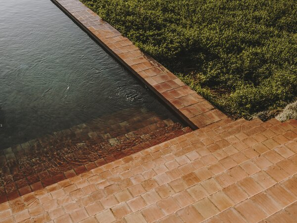 The steps that lead from the covered patio down to the pool are crafted by a local brand, creating a connection between the built form and the site.