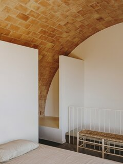 """The vaulted ceiling in the principal bedroom is based on the arc of a 21-foot-diameter circle that rises from its tangent with the ground-floor wall and culminates in the maximum regulatory height allowed, hence its asymmetry. It was the most costly part of the build, but """"it was worth it because it gives the space a unique character, combining tradition with a contemporary approach,"""" says architect Benjamin Iborra Wicksteed."""