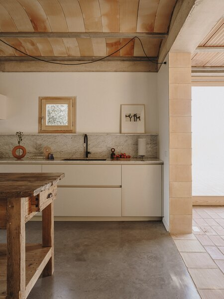 The kitchen features a marble backsplash and a precisely placed window. The floors and internal walls are also crafted from clay and concrete.