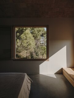 "A window in the principal bedroom. ""The relationship between interior and exterior is observant, contemplative, and subtle, due to the windows that frame the view,"" says architect Benjamin Iborra Wicksteed. ""We approached these window frames like hanging up paintings—although instead of art, it's views of nature."""