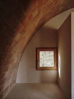 The vaulted ceiling above the principal bedroom is constructed from two layers of solid, hand-fired clay brick from local brand Rajoleria Llensa, and pieces of ceramic board from local brand Cerámiques Belianes.