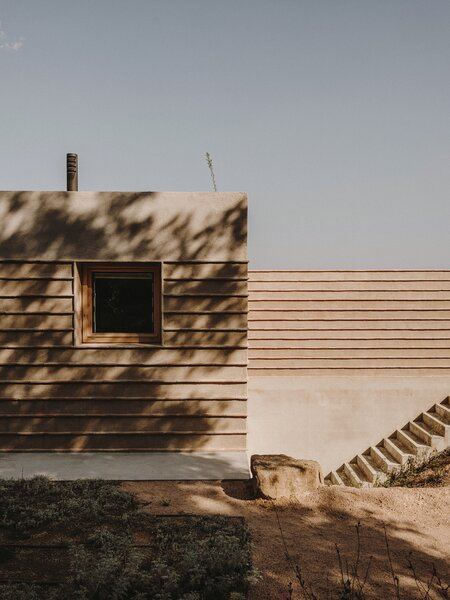 The clay used to construct the walls doesn't just have a structural role— it also creates various textures that help the home blend into the surrounding landscape. To keep within budget, the structure of the home was kept as simple as possible—with the notable exception of the soaring vaulted ceiling in the master bedroom.