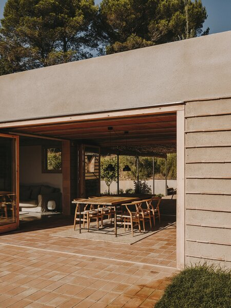 """For cross ventilation, the residents can open and close the large sliding doors around the porch, which the architect describes as """"the heart of the home."""" Likewise, windows are positioned to provide breezes when necessary."""
