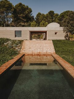 """Steps lead down the sloped site from the patio to the pool, allowing the home to """"drape"""" over the topography."""