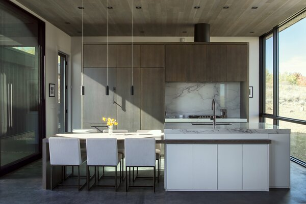 "The cabinetry in the kitchen is rift-sawn, dark-stained white oak that complements the ceilings and contrasts with the white walls. The dark-pigmented concrete floors were intentionally left untreated in order to convey a sense of time. ""As the home ages, the floor 'records' the construction process, foot traffic, wine spilled at birthday parties, drips of olive oil from anniversary dinners, watermarks from relaxing showers, and so on,"" says architect Hunter Gundersen. ""Every action will be subtly set in stone before it's quickly cleaned up or swept away. Over the years, a patina of life will build up, adding depth and beauty to the interior."""