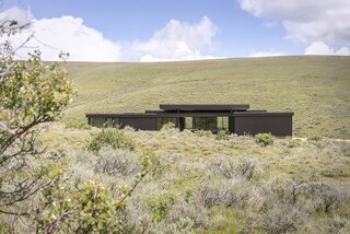 "The dwelling is located on the hill's brow, so it nestles into the slope just below a prominent cluster of quaking aspens where a resident bull moose lives. ""The lot is located in a sea of grass-covered hills,"" says architect Hunter Gundersen. ""Unlike much of the Rocky Mountains it isn't a craggy landscape full of cliffs, ravines, and broken rock faces. Instead, it's soft and rolling, like grassy ocean swells with an occasional rock-outcropping ship or tree-stand island. Like the outcroppings, the structure is low lying, dark, and embedded into the grass and sage—at home on the soft surface, but not apologetic nor blending in."""