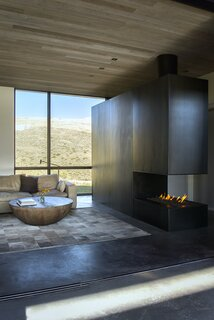 "The freestanding hearth serves multiple functions—it's a fireplace, a privacy screen to the master bedroom, an entry closet, and an art piece. ""The cantilevered structure is meticulously clad in raw industrial, hot-rolled steel sheets,"" says architect Hunter Gundersen. ""There is no glass, so the fire is open on all three sides. Like ballet, it looks easy and effortless, but in reality it's a labor of painstaking love."" The gas burner and steel substructure was fabricated and installed by yNot construction, and the metal cladding artwork was crafted by Parker Cook Design."