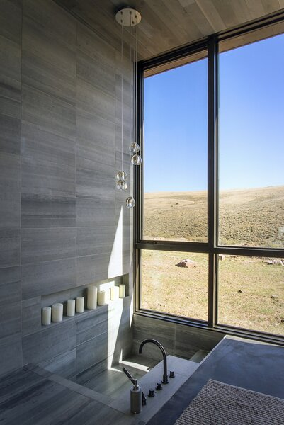 """""""The owner wanted the master bathroom to be spartan but elegant,"""" says architect Hunter Gundersen. """"He came across a recessed tub and loved the idea. There's something special about descending down into the architecture rather than sitting in an additive object on the architecture."""""""