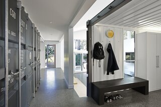 The front entrance leads into a shipping container that features a mud room, laundry and bathroom. This space has been opened up to the circulation space between the existing home and the new addition.
