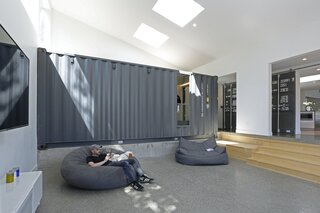 """We really wanted the rest of the house to be quiet in order to showcase the shipping containers as art objects,"" says Davis. ""So, we used a very simple materials palette: lots of big windows and doors to bring in light and open up to the yards; heated concrete floors, polished to reveal the aggregate; basic IKEA cabinets; sheetrock painted a gallery-like white; and some touches of light, natural wood to add warmth and texture."""
