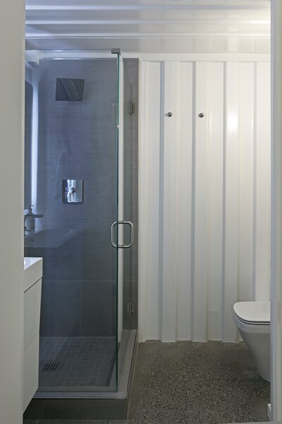 The small bathroom inside the shipping container at the entrance. The inside walls have been painted white to create a sleek, minimal appearance.